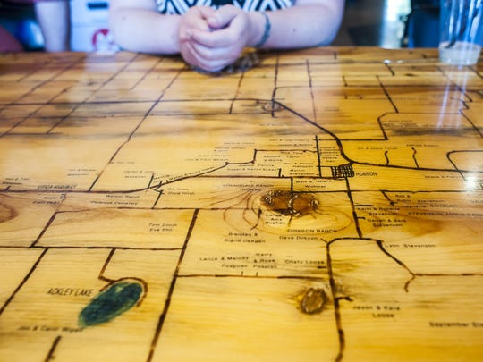 A map of Hobson, Ackley Lake and the surrounding area is woodburned on a table by Clint Carr, Liz Carr's father-in-law, in Hobson's Tall Boys Tavern.