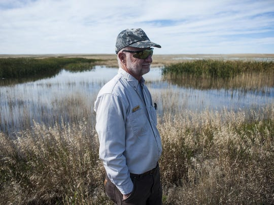 """Bob Johnson, deputy refuge manager, stands in front of the only unit filled with water that will be open for duck hunting at Benton Lake National Wildlife Refuge. """"This unit was built here to enhance breeding potential and it's just never been hunted,"""" Johnson said. The refuge hasn't received enough runoff to sustain water levels and the cost of pumping in water is steep with this year's bill estimated at $47,000."""