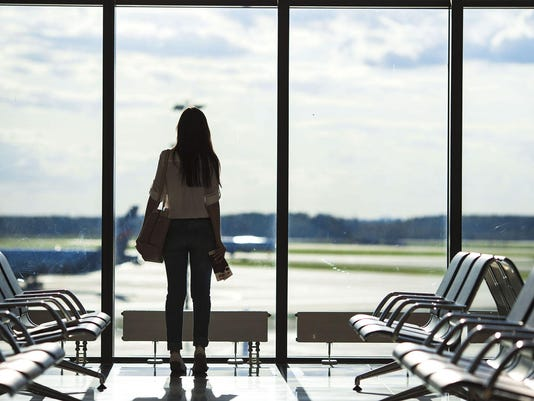 Silhouette of woman in airport lounge waiting for flight aircraft