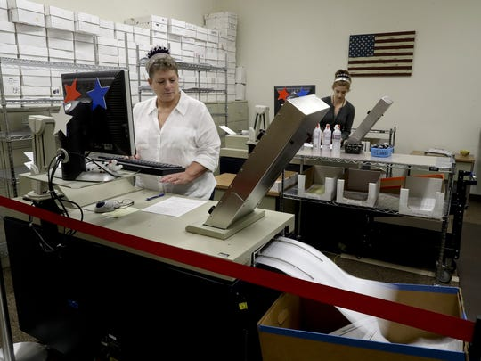 Shasta County election workers scan mail-in ballots at the Shasta County Elections Office in Redding during a recent election.