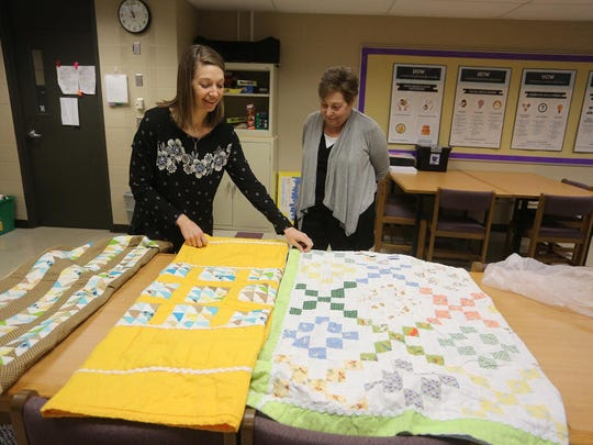 Teacher Johanna MacKenzie and hospice volunteer Earlene Ginter look over a quilt Ginter finished for MacKenzie's mother Carolyn Sheets. Ginter finished three quilts started by Sheets intended for her family. Ginter presented the final quilt to MacKenzie at Norwalk High School on March 8.