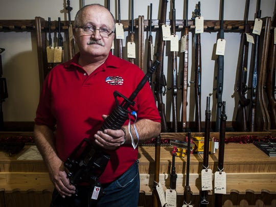 "Jim Mitchell holds a Colt M4 .22 in his shop Mitchell Supply. ""Anytime there is talk about guns, people think they have to go and buy the gun and then they get the ammunition to go with it,"" he said in 2015. The sale of guns and ammo is expected to dip significantly under the Trump Presidency."
