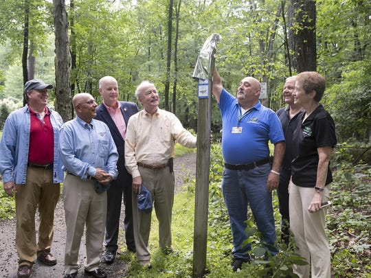 Unveiling the trail marker is Russell J. Nee of Morris Township, a board member of the September 11th National Memorial Trail Alliance. From left are alliance founder David G. Brickley, current president Andy Hamilton, Morris County Sheriff James Gannon, Congressman Rodney Frelinghuysen, Nee, Freeholder Director Douglas Cabana, and president of the Morris County Park Commission Betty Cass-Schmidt. National Memorial Trail Alliance, in conjunction with the Morris County Park Commission, celebrates the unveiling of the first trail blaze on the September 11th National Memorial Trail, a 1,300 mile tribute to first responders and those who perished on September 11th 2001. The marker is at the end of Dolly Bridge Road, Randolph, NJ. Saturday, July 15, 2017.