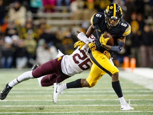 Iowa's Ihmir Smith-Marsette (6) catches a pass and is tackled by Minnesota's Justus Harris during an NCAA college football game Saturday, Oct. 28, 2017, in Iowa City. (Brian Powers/The Des Moines Register via AP)