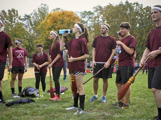 In this Oct. 19, 2013, photo, students from Lafayette College in Easton, Pa., attending an annual Harry Potter festival in Philadelphia. They hold brooms while waiting to play a match of a fictional sport described in the fantasy series, Quidditch.