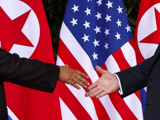 In this June 12, 2018, file photo, President Donald Trump, right, reaches to shake hands with North Korea leader Kim Jong Un at the Capella resort on Sentosa Island in Singapore.