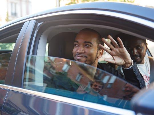 Man waving from car.