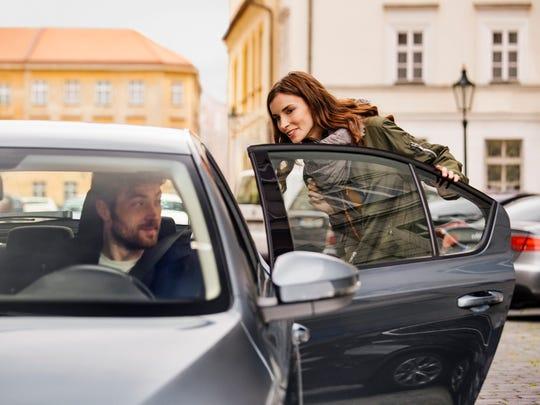 A woman gets into a car.