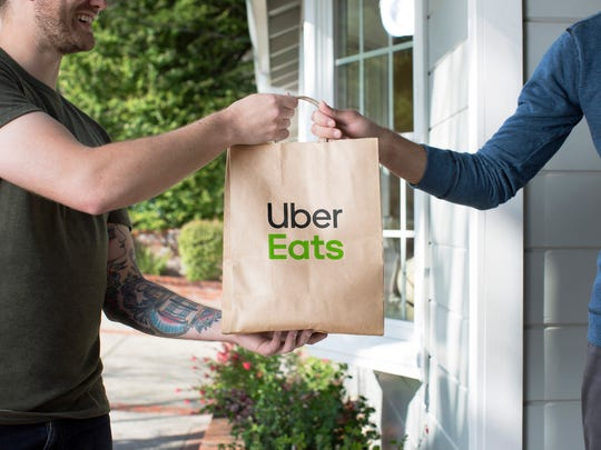 Man handing a bag with the Uber Eats logo to another man.
