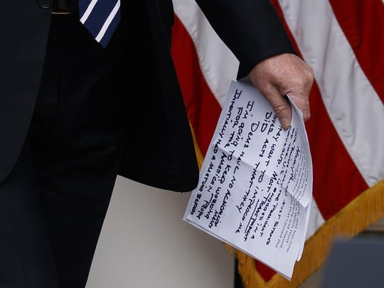 "In this May 22, 2019, photo, President Donald Trump carries notes that say ""they want to impeach me"" as he walks from the Oval Office to speak in the Rose Garden of the White House in Washington. (AP Photo/Evan Vucci)"