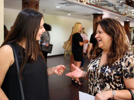 Aly Velasquez, left, exchanges business cards with Theresa Peters of the Shreveport-Bossier Hotel and Lodging Association at a recent meeting.