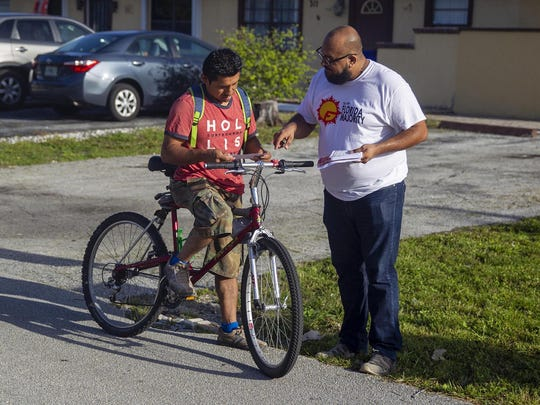 Carlos Naranjo, right, gives Michael Cruz a know-your-rights flyer in Pompano Beach, Fla., on Sunday, July 14, 2019. The handout explains what rights undocumented immigrants have in case they encounter ICE officials. Cruz is not undocumented. (Charlie Ortega Guifarro/Miami Herald/TNS)