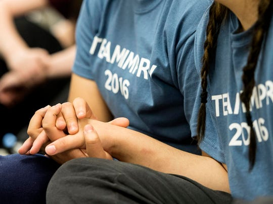 Two youth participants support each other by holding hands as they watch a performance dealing with the death of a loved one at the Youth Rehabilitation and Treatment Center in Geneva, Neb., in 2016.