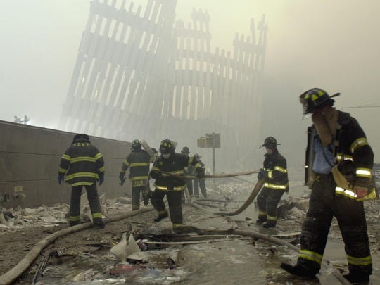 FILE - In this Sept. 11, 2001, file photo, firefighters work beneath the destroyed mullions, the vertical struts that once faced the outer walls of the World Trade Center towers, after a terrorist attack on the twin towers in New York. Sept. 11 victims' relatives are greeting the news of President Donald Trump's now-canceled plan for secret talks with Afghanistan's Taliban insurgents with mixed feelings. (AP Photo/Mark Lennihan, File)