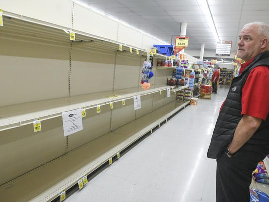 Dean Walker, president of Boyer's Food Markets, looks over the empty toilet-paper shelves at a Boyer's in Orwigsburg, Pa., Tuesday, March 17, 2020. Walker posted on Facebook asking customers to be patient, don't hoard food and work together during the coronavirus outbreak. (Jacqueline Dormer/Republican-Herald via AP)
