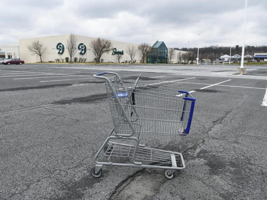In this Tuesday, March 17, 2020, photo, a lone shopping cart sits in an empty parking lot near a shopping mall closed due to coronavirus concerns in Pottsville, Pa. In Pennsylvania last week, 12,200 people filed for unemployment insurance. In just a single day this week, that number exploded beyond 50,000. In neighboring Ohio, 48,460 people filed for unemployment Sunday and Monday, compared to less than 1,900 over the same period the week before. It's the same story in state after state, as millions of displaced Americans lose their jobs amid the widening shutdowns to contain the coronavirus. (Jacqueline Dormer/Republican-Herald via AP)
