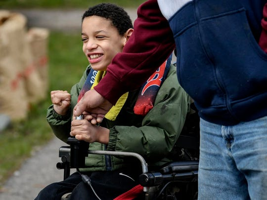 Brian Hagler, right, helps his son Chris, 8, with steering his wheelchair.