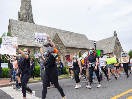 Protestors pass a church on Main Street in Moorestown on Tuesday.