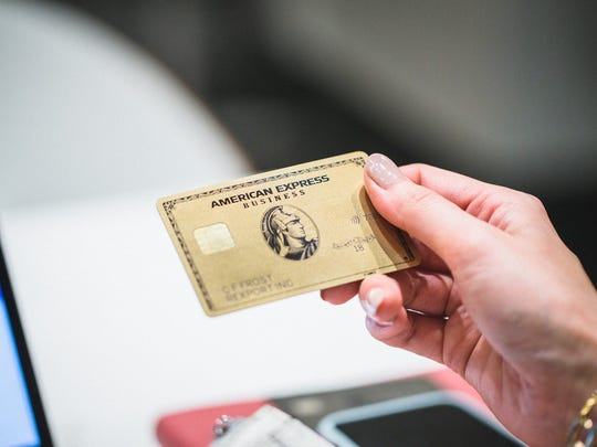 A person holding up an American Express gold business card.