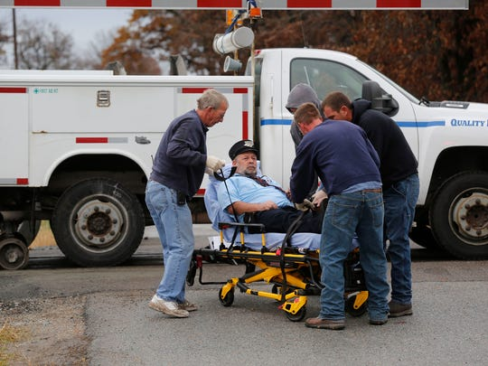 An Amtrak employee is taken to an ambulance after an Amtrak train struck a semi-truck about 8:30 a.m. Tuesday, Oct. 28, 2014, just east of the intersection of White County Road 200 North and Indiana 421 near Reynolds, Ind. The train was northbound and heading to Chicago when the accident took place. White County Sheriff Pat Shafer said 14 people complaining of pain were taken to local hospitals after the collision. The truck driver was not among the injured, he said.  (AP Photo/Journal & Courier, John Terhune)