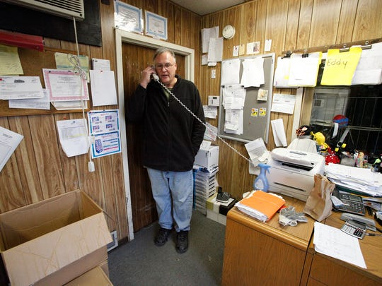 Douglas Lallier, who turns the tables on scammers by trying to scam them, talks on the phone with a scammer in his office in Old Bridge.