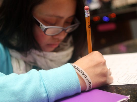 "Thirteen-year-old cancer survivor Kaela Cruz wears a ""Kids get cancer too"" bracelet while working on her math homework, Thursday, January 29, 2015, in Sayreville, NJ. Jason Towlen/Staff Photographer"