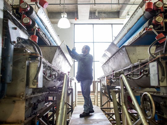 Todd Moore, an operator in the incinerator building at the Buncombe County's Metropolitan Sewerage District wastewater treatment plant, checks on the belt presses that remove water from sludge. The plant's managers plan to upgrade the current system, including the incinerator, to meet 2016 EPA environmental standards for emissions, particularly mercury.