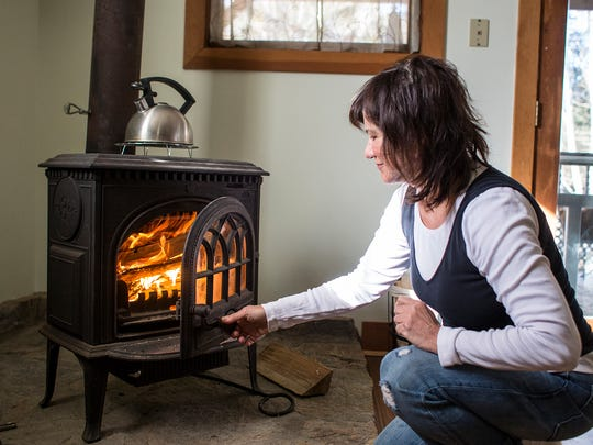 Marilyn Ball stokes her wood-burning stove Saturday in the basement of her North Asheville home. Ball said she used to use solely wood heat at her former home but now uses a combination of a wood stove and heat pump during the colder months.