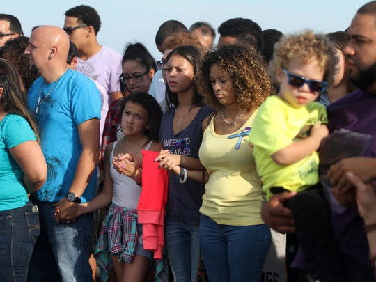 People join hands in prayer during a suicide prevention walk on the crest of the Victory Bridge, Sunday, September 28, 2014, in Perth Amboy, NJ.  Photo by Jason Towlen