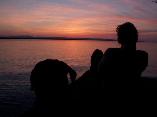 A silhouette of a woman and dog along the west shore of South Hero.