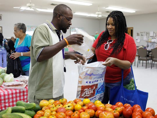 Christian Easton, right, of Shively, buys chicken from farmer Anwar Barbour on her trip to pick up fresh fruit and vegetables at the Shawnee Neighborhood Fresh Stop, held at Redeemer Lutheran Church . She has relied on food stamps for several months while her husband was laid off.