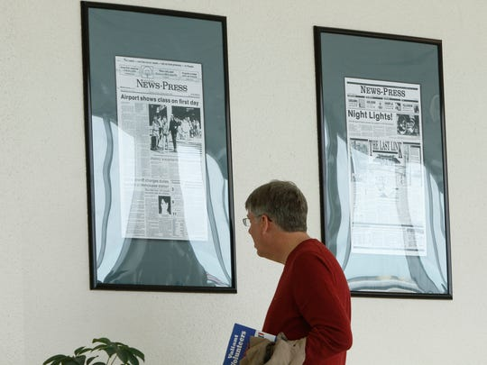 Passengers walk past a series of historic front pages from The Fort Myers News-Press Friday, January 16 at Southwest Florida International Airport.