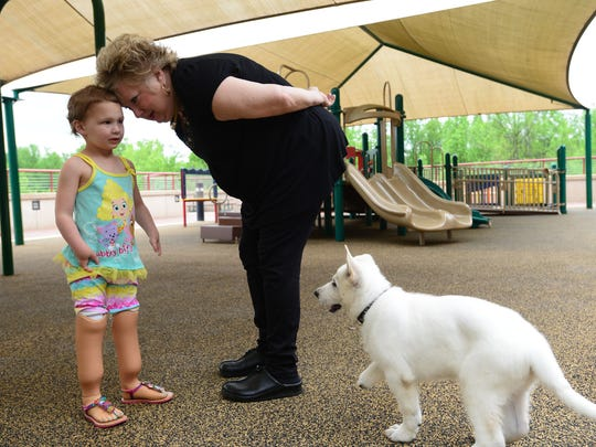 Sapphyre Johnson, left, 3, who has two prosthetic feet, speaks with Karen Riddle, center, who is giving Johnson a new puppy named Lt. Dan. The 9 month-old puppy was born without a front paw.
