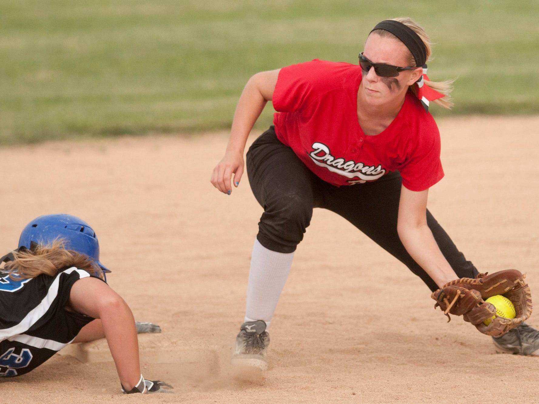 Franklin runner Shelby Taylor makes her way back to second base before the tag by New Palestine shortstop Adie Lorsung during the Sectional 13 softball championship game at Franklin Community High School, Wednesday, May 28, 2014.