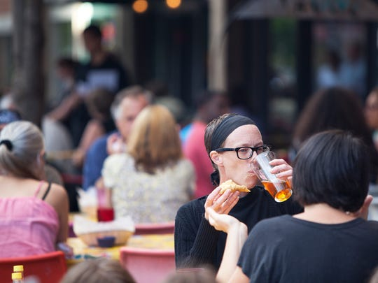 Christina Coleman from Ithaca enjoys food and a beer outside Viva Taqueria along restaurant row on North Aurora Street in Ithaca.
