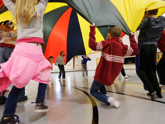 Second through 5th grade students play with a parachute in physical education during the Wildcat Creek Home Educator's Cooperative Tuesday, December 2, 2014, at Kossuth Street Baptist Church. Homeschooled students meet from 9 a.m. til noon every other Tuesday for a variety of classes at the church.