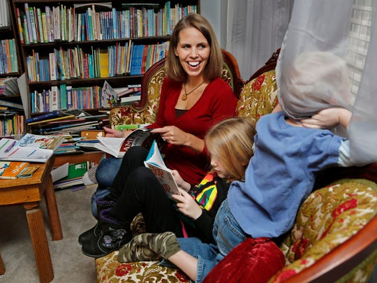Cara Putman laughs as her son Daniel, 4, pokes his head under curtains to look outside during homeschooling reading lessons with sister Rebecca, 6, Monday, November 24, 2014, in their Lafayette home. An upstairs room serves as the homeschooling classroom for all four Putman children. Cara Putman was homeschooled as a child growing up in Nebraska.