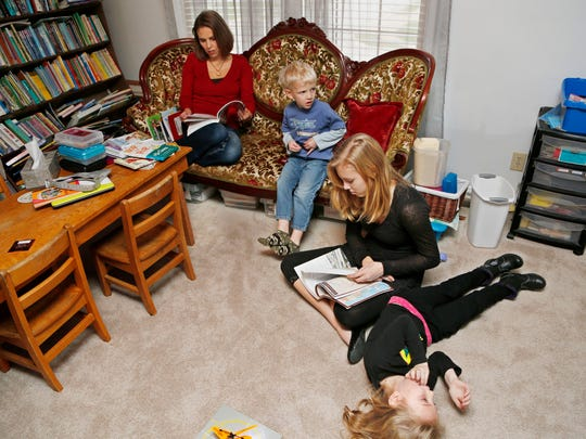 Cara Putman, upper left, quizes her daughter Abigail, 14, on American history as younger children Rebecca, 6, and Daniel, 4, wait to begin their homeschooling lessons Monday, November 24, 2014, in their Lafayette home. An upstairs room serves as the homeschooling classroom for all four of Putman's children. Cara Putman was homeschooled as a child growing up in Nebraska.