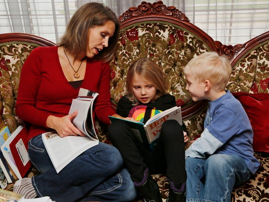 Younger brother Daniel, 4, peeks in as Cara Putman reads with her daughter Rebecca, 6, during homeschooling Monday, November 24, 2014, in their Lafayette home. An upstairs room serves as the homeschooling classroom for all four Putman children. Cara Putman was homeschooled as a child growing up in Nebraska.