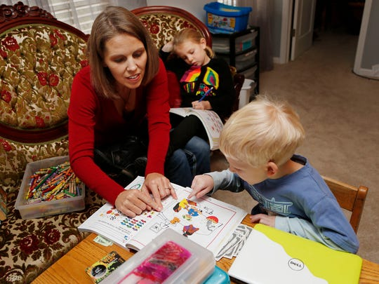 Cara Putman works with her son Daniel, 4, on math as sister Rebecca, 6, background, completes math problems in her workbook Monday, November 24, 2014, in their Lafayette home. An upstair room serves as the homeschooling classroom for all four of Putman's children. She, too, was homeschooled as a child growing up in Nebraska.