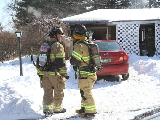 Marion City firefighters pause in front of a still smoldering home after taming a house fire at 808 Underwood on Monday morning, Mar. 2, 2015. The fire appeared to have started on a living room sofa. James Miller/The Marion Star