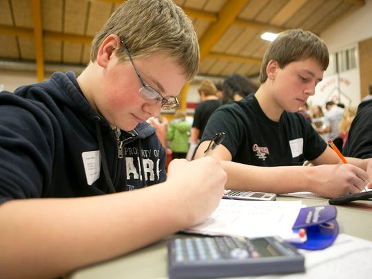 Pittsville eighth-graders Karl Durrant, left, and Tyler Gardner, right, work on figuring out how much their home furnishings will cost during the Reality Store at Spencer Middle School, Tuesday, March 10, 2015. The Reality Store is put on by the Marshfield Area Chamber of Commerce and Industry and included students from Stratford, Pittsville, and Spencer.