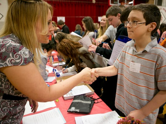 Coldwell Banker Realty's Jennifer Elmhorst shakes Spencer eighth-grader Devin Mayfield's hand before they look at possible houses Mayfield could buy at the Reality Store at Spencer Middle School, Tuesday, March 10, 2015.