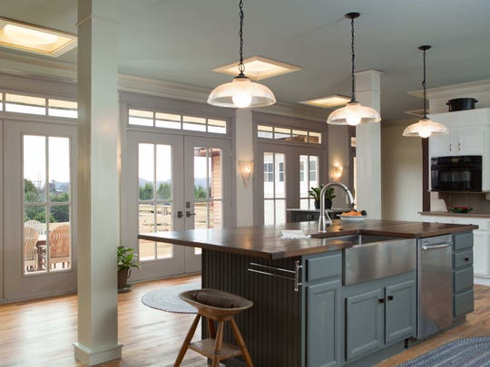 One of the kitchen's two islands is topped by a handcarved walnut top with a stainless farm sink.