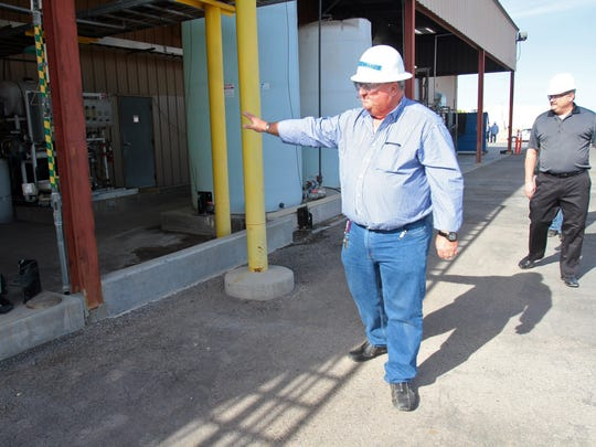 Simbol Materials' then-director of manufacturing, David Edwards (front), and then-vice president of business development Tracy Sizemore give a tour of the company's demonstration plant on Jan. 8, 2014.
