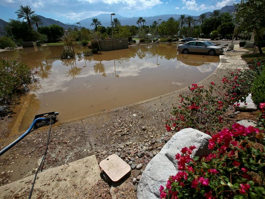 A day after the September storm, cars remained stuck in a flooded parking lot at the Casitas Las Rosas condominium and vacation rental complex at Desert Club Drive and Calle Tampico in La Quinta.