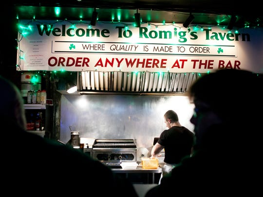 Customers have a drink at the bar at Romig's Tavern on Friday.