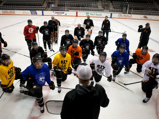 The RIT women's hockey team listens to assistant coach Matt Woodard during practice in the Polisseni Center.