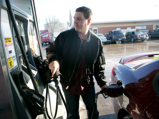 """Anthony Wolf of Marshfield fills up his car at $2.29 per gallon at the Kwik Trip on North Central Avenue in Marshfield, Friday, Jan. 2, 2015. Wolf said, """"I wonder what is behind the gas prices going down but I'm not complaining."""""""
