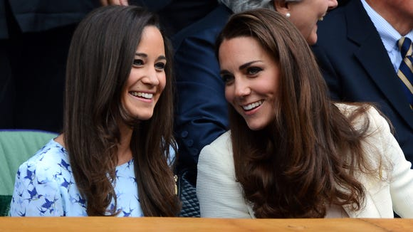 Duchess Kate and sibling Pippa Middleton engage in some sisterly bonding in the Royal Box at Wimbledon in 2012.